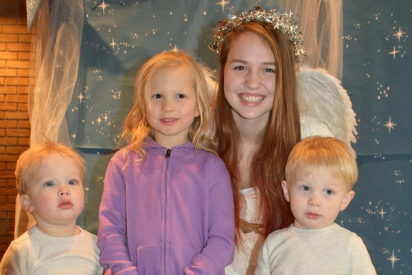 Teen girl dressed as a angel with several small children