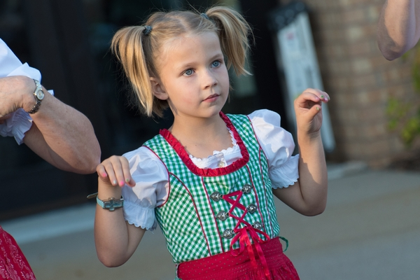 A young girl in lederhosen does the chicken dance