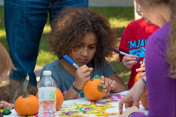 A young girl decorates a pumpkin