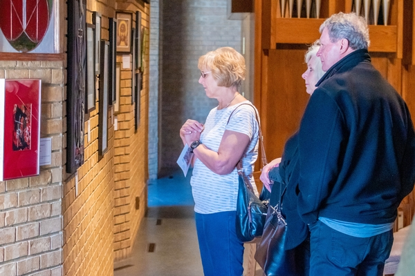 Several adults look at art in Cross View's sanctuary