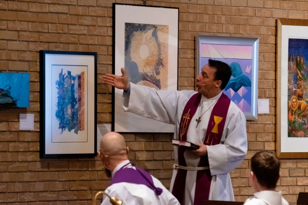 Pastor Steve Wheeler points to art in the sanctuary during a sermon