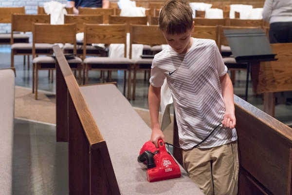 A young boy vacuums a church pew