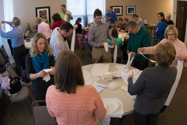 A crowded room of people wrapping bandages on a Service Sunday