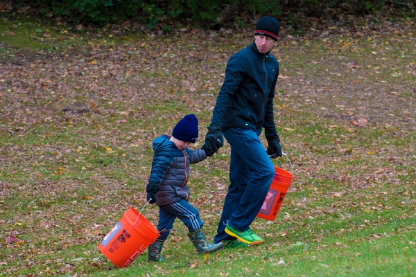A father and son walk through grass and leaves with two buckets