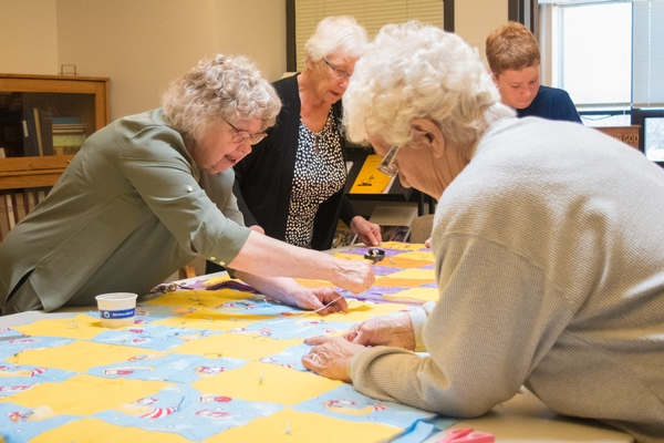 Senior citizens making quilts on a Service Sunday