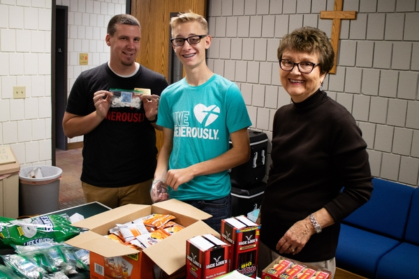 A teen boy and two adults making care packages for college students