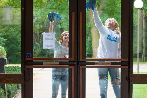 Two girls washing Cross View's front doors.
