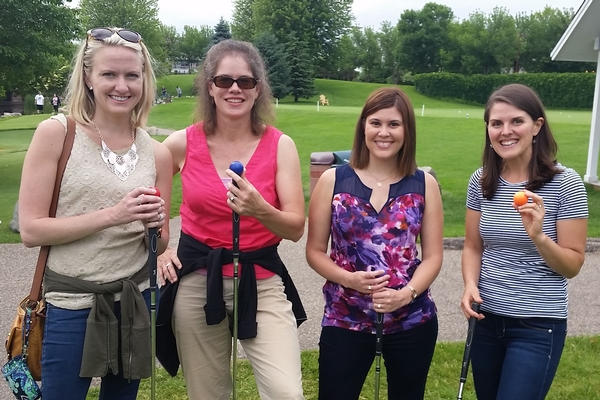 Four young adult women mini golfing