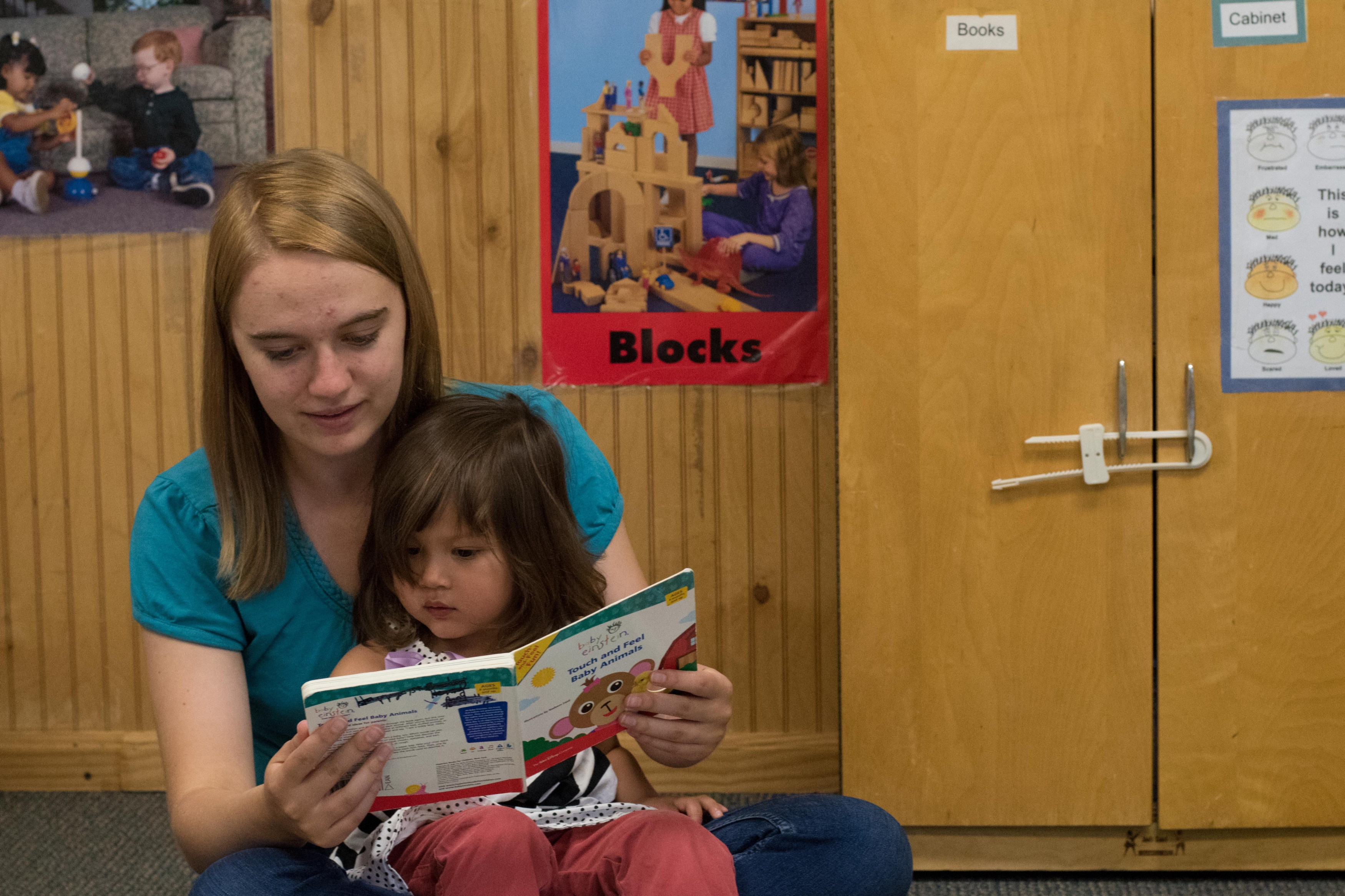 A female ECC teacher reads to a child.