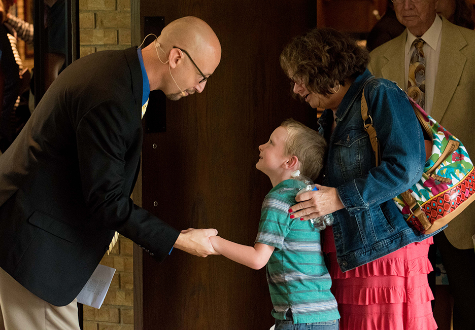 Pastor Toby shaking hands with a young boy and his grandmother