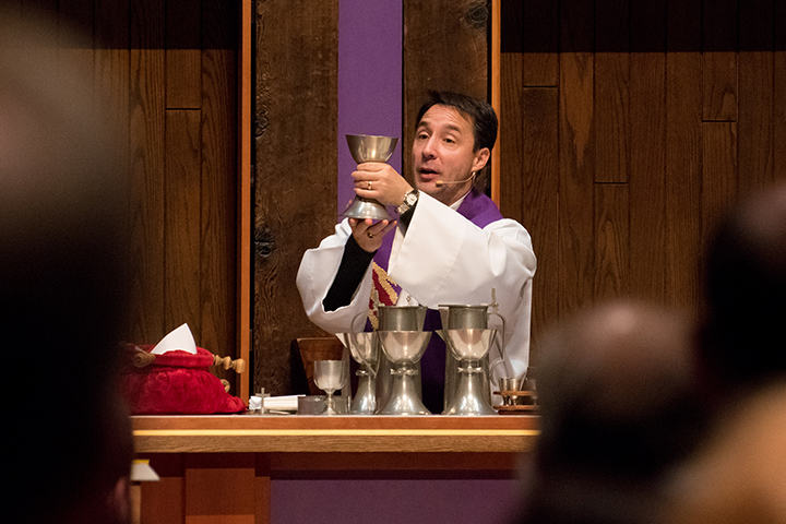 Pastor Wheeler holding the communion chalice.