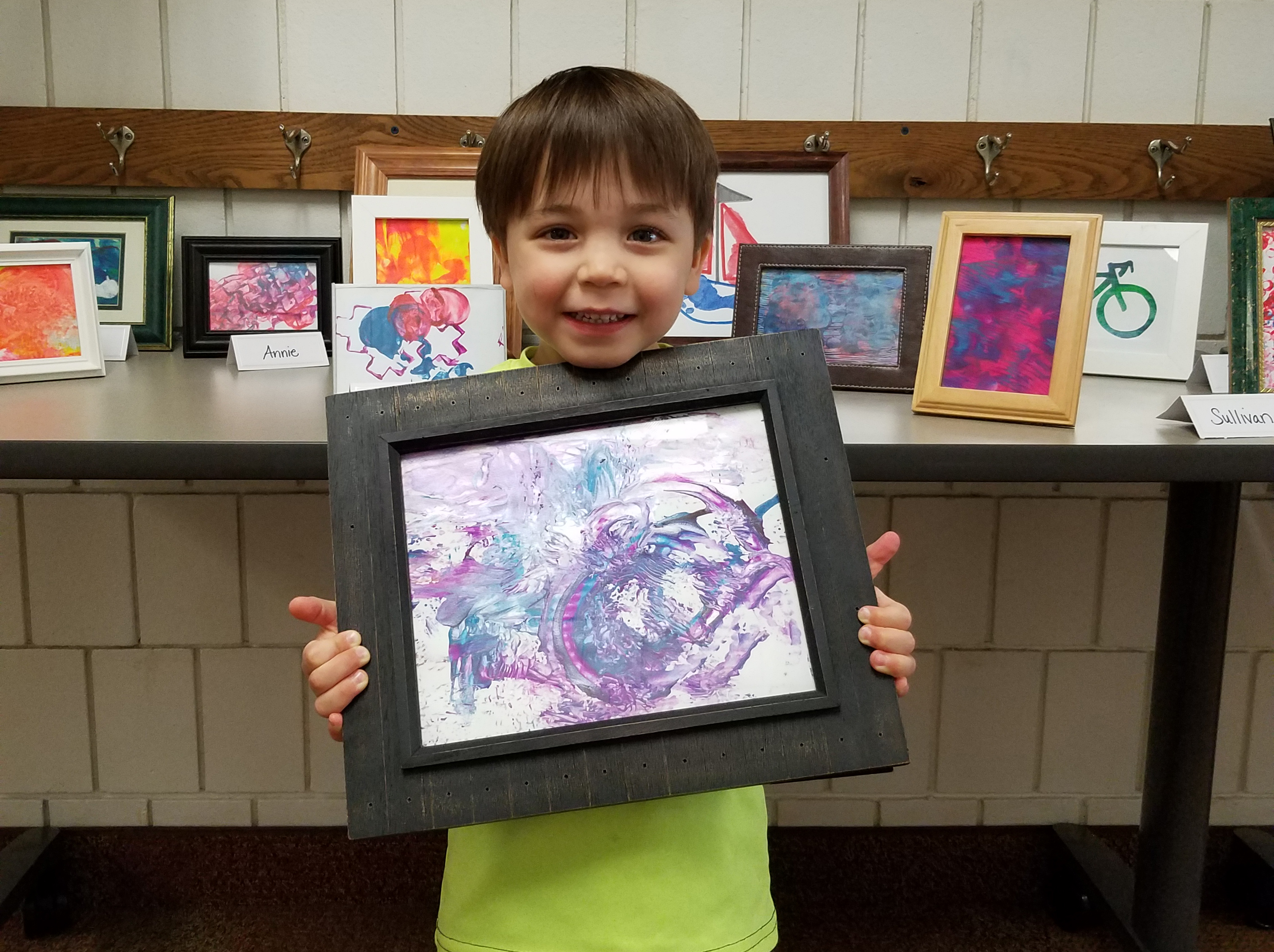 An ECC boy holds his framed painting