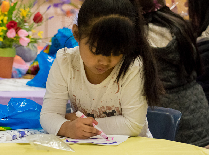 A young girl drawing.