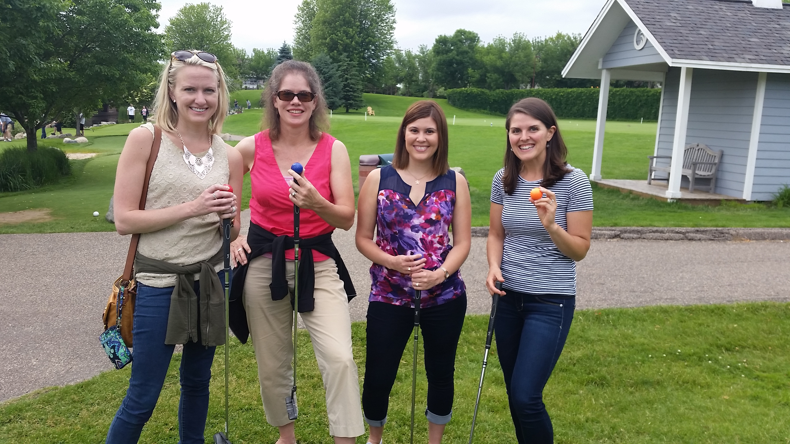 Four young adult ladies miniature golfing